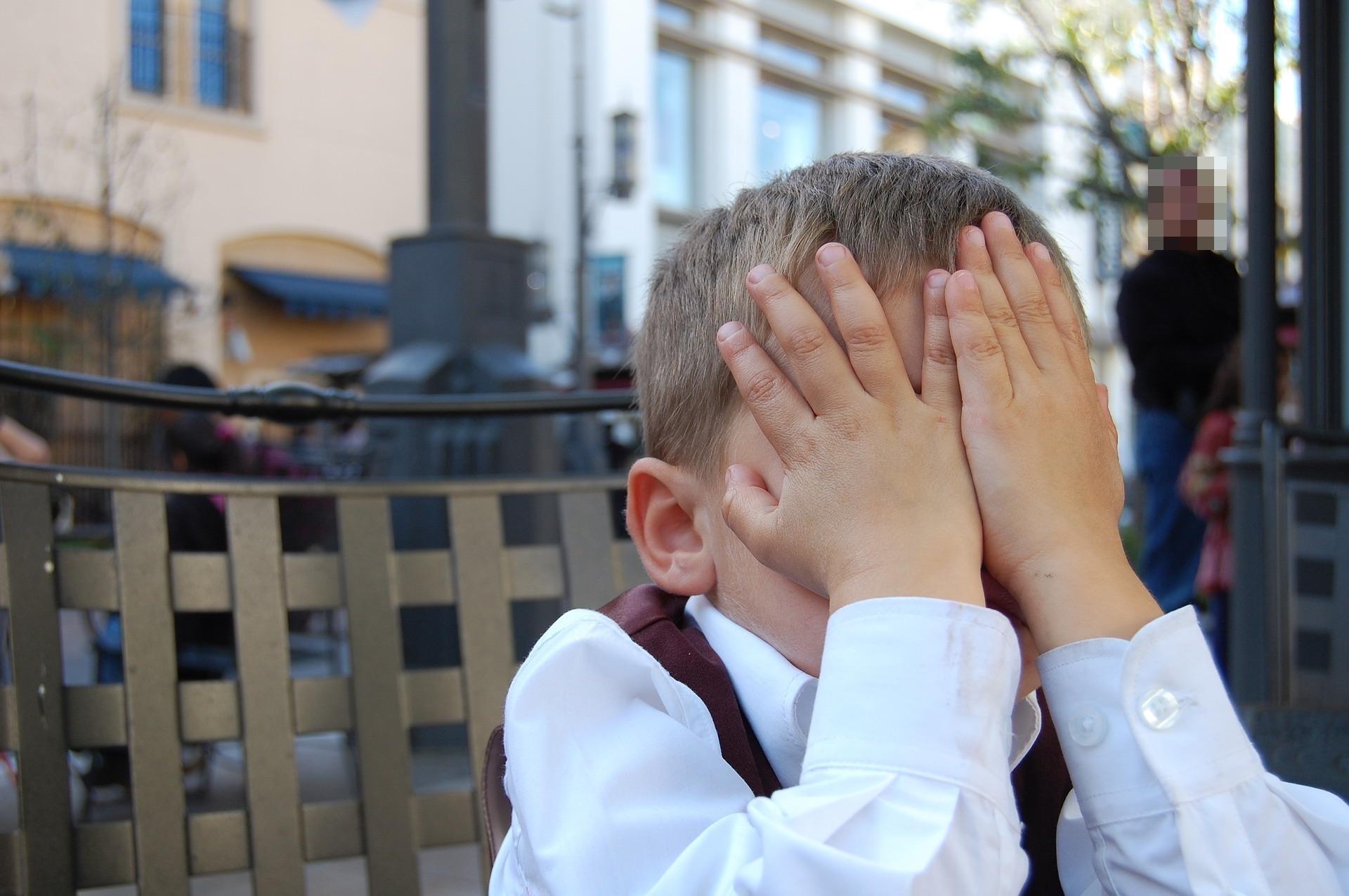 Boy hiding behind hands
