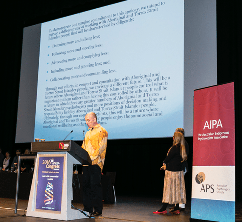APS apology to Aboriginal and Torres Strait Islander Peoples read by Tim Carey. Also on stage is Professor Pat Dudgeon, from the Bardi people of the Kimberley in Western Australia, who was the first Aboriginal psychologist to graduate in Australia and has led work on Social and Emotional Wellbeing. Credit: APS