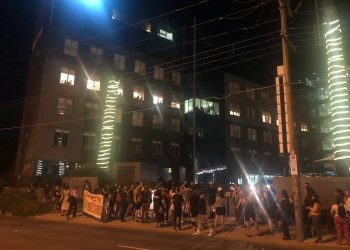 """Refugee advocates  hold a vigil outside the Mantra hotel in Melbourne this week, amid concern that """"Medevac"""" refugees – watching from the windows above – were going to be suddenly moved to a new facility. Photo: Marie McInerney"""